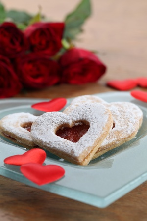 Shortbread hearts on a plate, confetti and red roses. Shallow dof photo