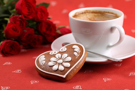 red cup: Gingerbread heart with coffee and red roses on red background. Shallow dof