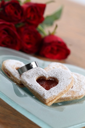 Titanium engagement ring with shortbread hearts on a plate and red roses. Shallow dof photo