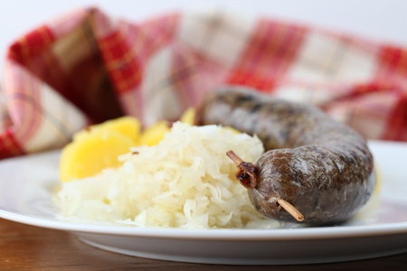 Traditional Czech white pudding made of pork, groats and various spices with potatoes and sauerkraut photo