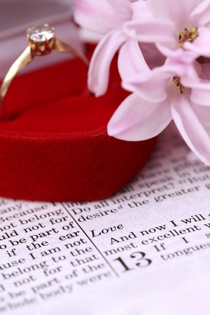 Gold engagement ring with diamond on the Bible open to 1st Corinthians 13, a passage about love. Shallow dof photo