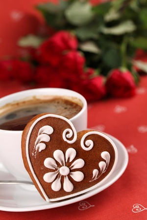 valentine day cup of coffee: Gingerbread heart with coffee and red roses on red background. Shallow dof