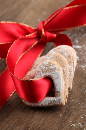Red ribbon with shortbread hearts. Shallow dof photo