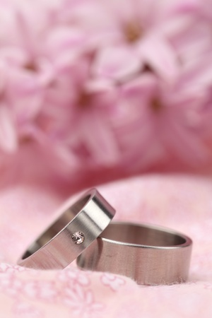 Titanium wedding rings on pink background with hyacinth. Shallow dof photo