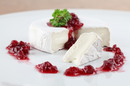 Camembert with cranberry jam and parsley on white plate. Shallow dof photo