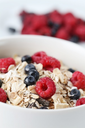 Granola with fresh organic raspberries and blueberries. Shallow DOF Stock Photo