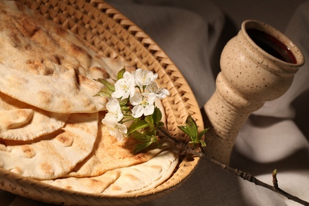 Chalice with red wine and pita bread in a basket photo