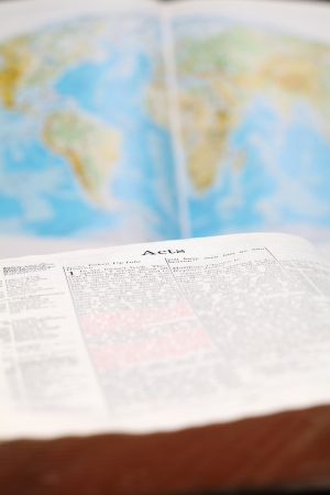 Bible open to the Book of Acts (the book that describes spreading the Gospel to the World) and a world map in the background. World missions concept. Stock Photo - 8878182