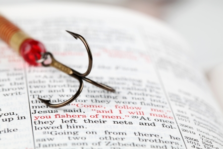 fishers: Fishing hook on the Bible with focus on Matthew 4:19 where Jesus calls disciples to be fishers of men Stock Photo