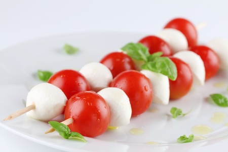 Caprese salad. Cherry tomatoes and mozzarella on skewers, garnished with basil leaves and olive oil Stock Photo