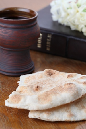 last supper: Chalice with red wine, pita bread, Holy Bible and white hyacinth Stock Photo