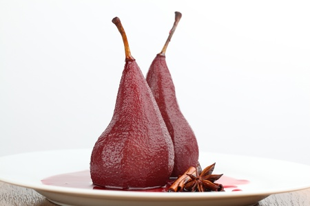 Poached pears in red wine with cinnamon and anise. Shallow dof Standard-Bild