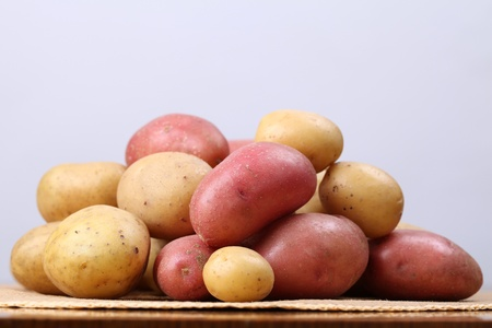 red straw: Red and white organic potatoes on a straw mat. Shallow dof Stock Photo