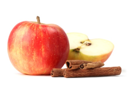 Apples and cinnamon sticks on white background. Shallow dof