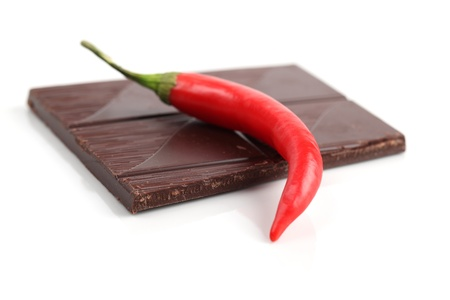Red chili pepper and dark chocolate on white background. Shallow dof photo