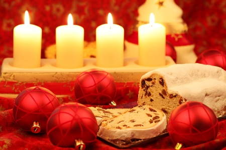 Christmas stollen with ornaments and candles on red background photo