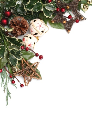 holly berry: Christmas border with jingle bells, stars and other Christmas ornaments and decorations isolated on white. Shallow dof