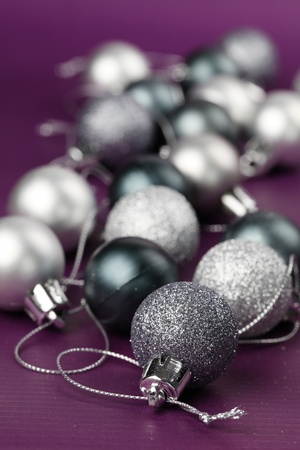 Silver Christmas ornaments on purple background. Copy space photo