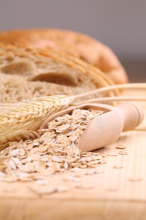 wooden scoop: Wooden scoop with oats and fresh bread in background