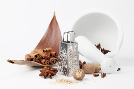 Nuez moscada, clavo de olor, an�s y canela con rallador y el mortero sobre fondo blanco. Dof bajo Foto de archivo - 11481051