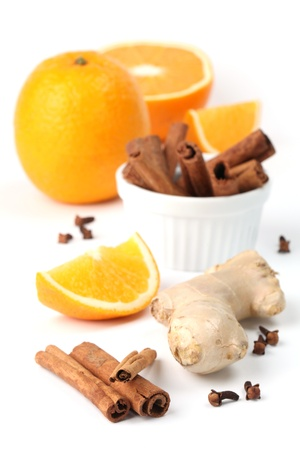 Ingredients for winter hot drink. Orange with cinnamon and ginger on white background photo