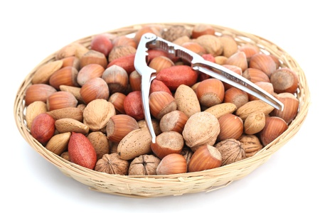 Basket with hazelnuts, walnuts, almonds and pecans with a nutcracker isolated on white background. Shallow dof photo