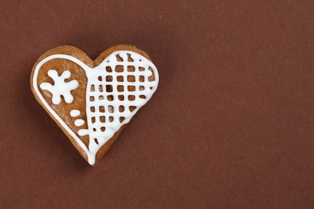 Gingerbread heart on brown background photo