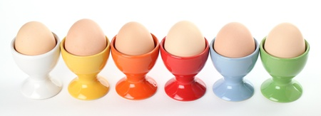 Close-up of a row of colorful eggcups with brown chicken eggs. Shallow dof photo