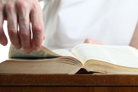 leyendo la biblia: El hombre dar vuelta la p�gina de la Biblia. Dof bajo Foto de archivo