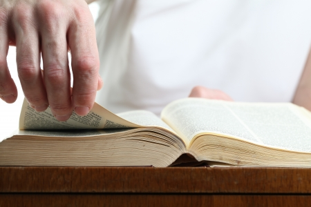 Man turning the page of the Bible. Shallow dof Stock Photo