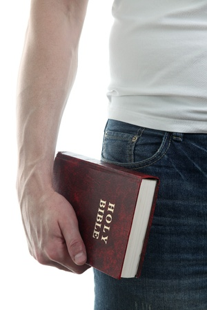 holding close: Man holding the Holy Bible, isolated on white background
