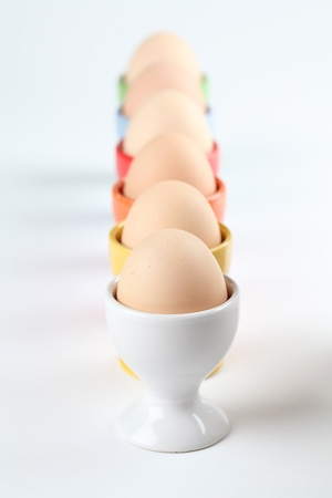Close-up of a row of colorful eggcups with brown chicken eggs. Shallow dof Stock Photo - 12199979