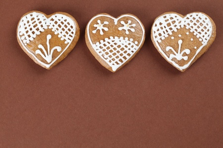 Gingerbread hearts on brown background photo