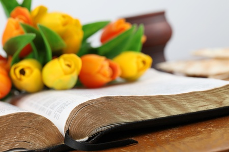 Close-up of an open Bible with a bouquet of colorful tulips. Shallow dof photo