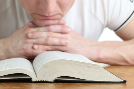 Man praying with the Bible. Focus on the Bible photo