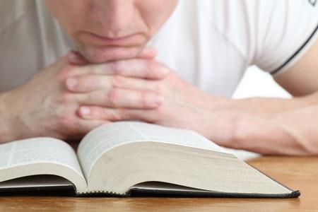 vangelo aperto: Uomo che prega con la Bibbia. Concentrarsi sulla Bibbia Archivio Fotografico