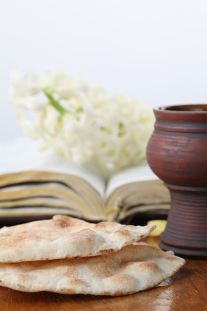 Communion. Chalice with red wine, pita bread, Holy Bible and white hyacinth photo