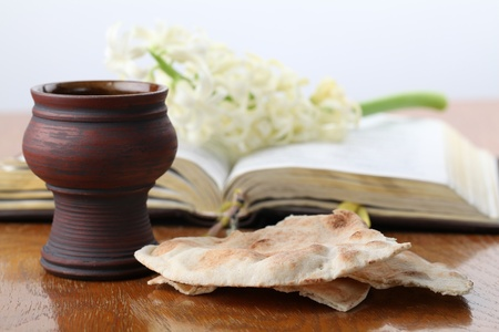 Communion. Chalice with red wine, pita bread, Holy Bible and white hyacinth