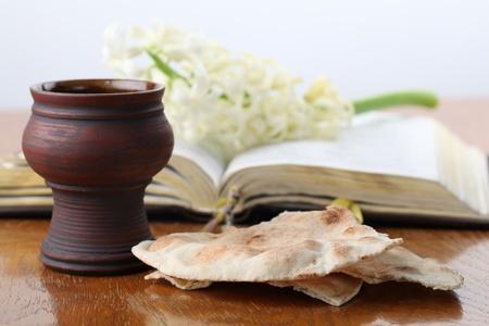 comunione: Comunione. Calice di vino rosso, pane pita, Sacra Bibbia e giacinto bianco