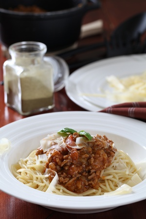 Spaghetti with bolognese sauce, cheese and basil photo