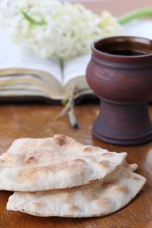 bible ouverte: La sainte communion Calice avec du vin rouge, pain pita, la Sainte Bible et de jacinthe blanche Banque d'images