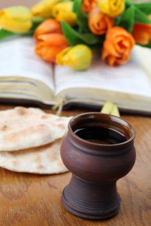 Holy communion  Chalice with red wine, pita bread, Holy Bible and colorful tulips photo