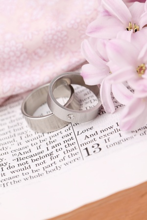 Titanium wedding rings on the Bible open to 1st Corinthians 13, a passage about love  Shallow dof photo