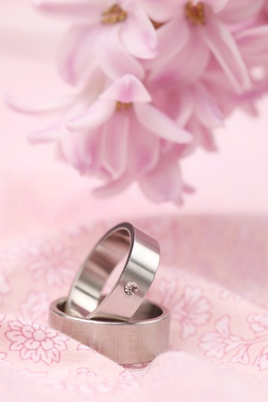 Titanium wedding rings on pink background with hyacinth  Shallow dof photo