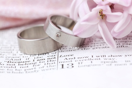 scripture: Titanium wedding rings on the Bible open to 1st Corinthians 13, a passage about love  Shallow dof Stock Photo