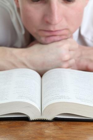 vangelo aperto: L'uomo studiando la messa a fuoco Bibbia sulla Bibbia Archivio Fotografico