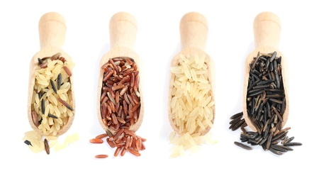 Wooden spoons with various kinds of rice on white background photo