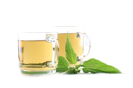 stinging nettle: Nettle and freshly made nettle tea in glass cups isolated on white background  Shallow dof, focus on nettle Stock Photo