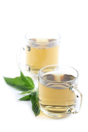 Nettle and freshly made nettle tea in glass cups isolated on white background  Shallow dof photo