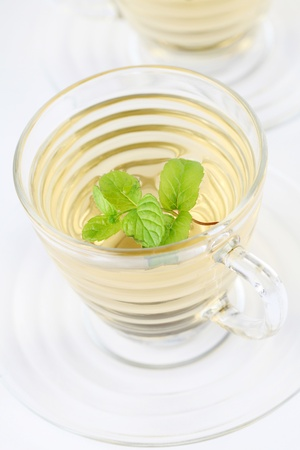 detoxification: Mint leaf and freshly made mint tea in glass cups isolated on white background  Shallow dof Stock Photo
